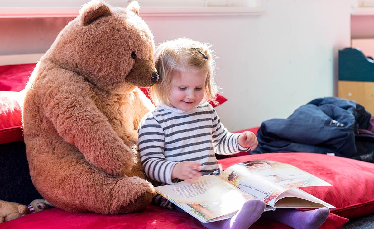 Kleines Mädchen liest einem Bären in der Stadtbibliothek Aurich vor